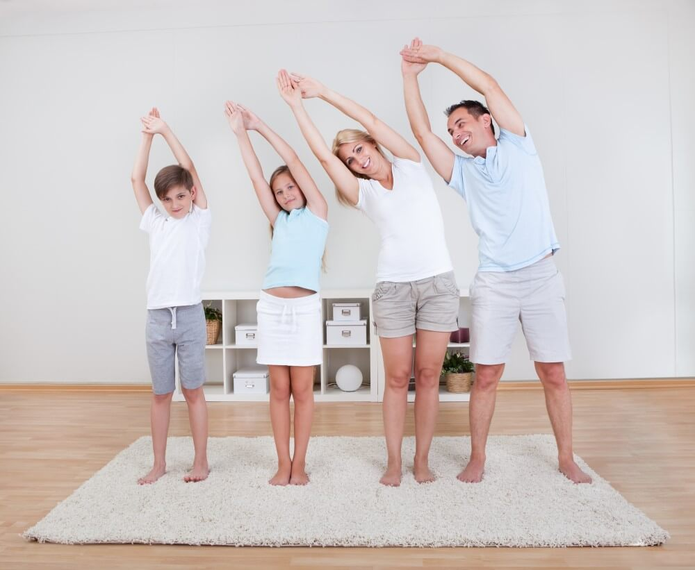 family practicing yoga together in their lounge room