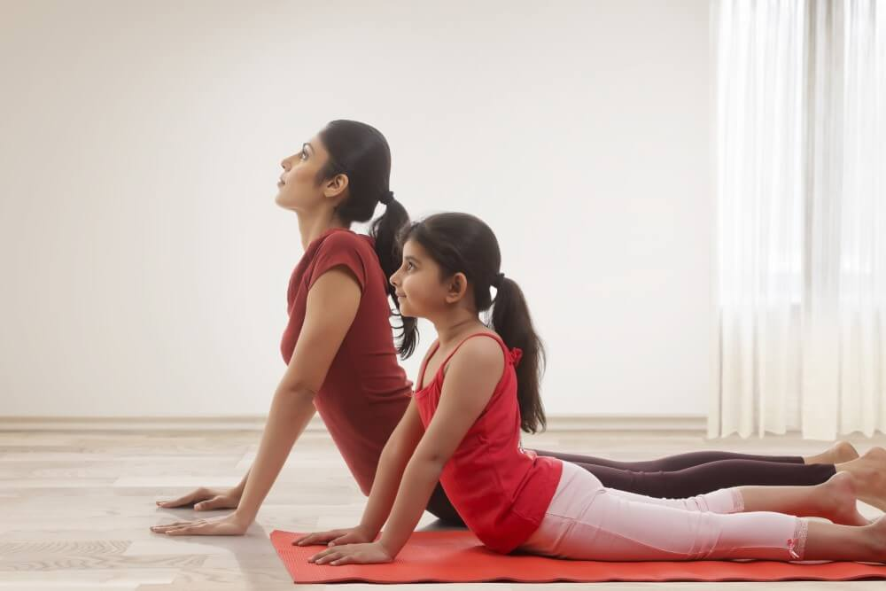 mother and daughter practiving yoga laying on floor with hands pressing up into cobra pose